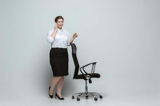 Junge kaukasische frau in freizeitkleidung auf grau. körperpositiver weiblicher charakter, übergröße