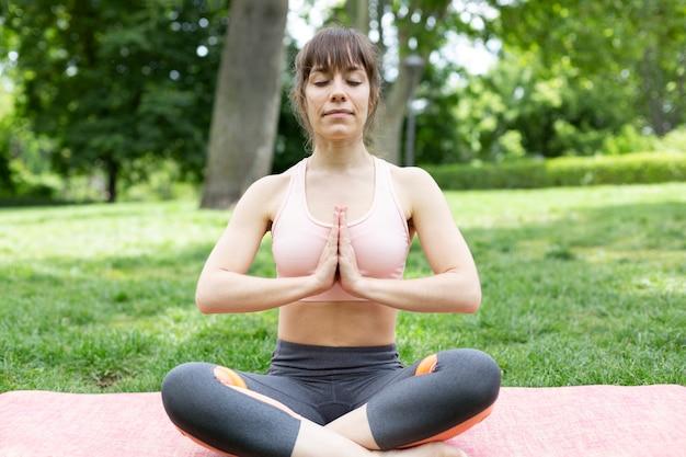 Junge kaukasische frau in meditationshaltung im freien. platz für text.