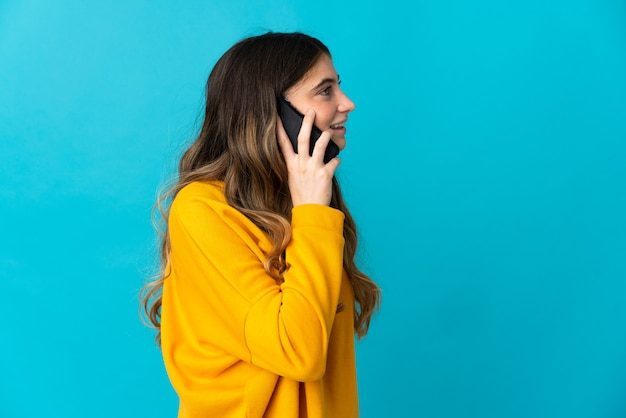 Junge kaukasische frau isoliert auf blau, die ein gespräch mit dem mobiltelefon mit jemandem hält