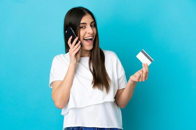 Junge kaukasische frau isoliert auf blauem hintergrund, die ein gespräch mit dem mobiltelefon führt und eine kreditkarte hält