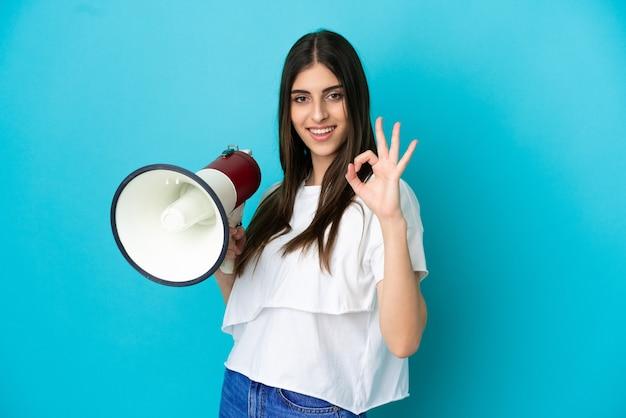 Junge kaukasische frau isoliert auf blauem hintergrund, die ein megaphon hält und ein ok-zeichen mit den fingern zeigt
