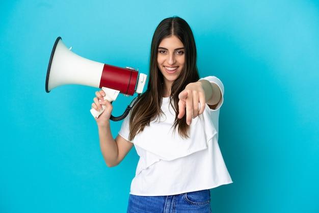 Junge kaukasische frau isoliert auf blauem hintergrund, die ein megaphon hält und lächelt, während sie auf die vorderseite zeigt