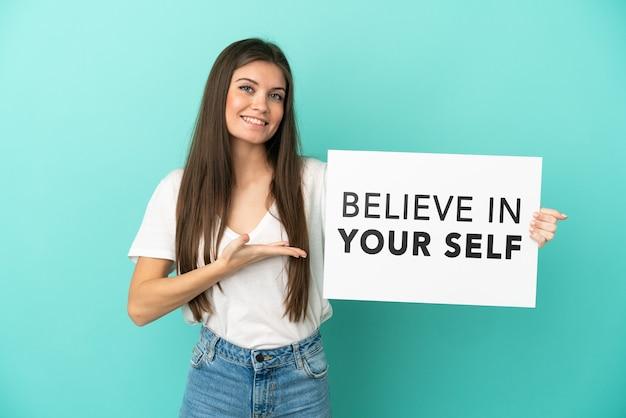 Junge kaukasische frau isoliert auf blauem hintergrund, die ein plakat mit dem text believe in your self hält und darauf zeigt