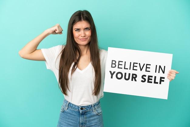 Junge kaukasische frau isoliert auf blauem hintergrund, die ein plakat mit dem text believe in your self hält und eine starke geste macht