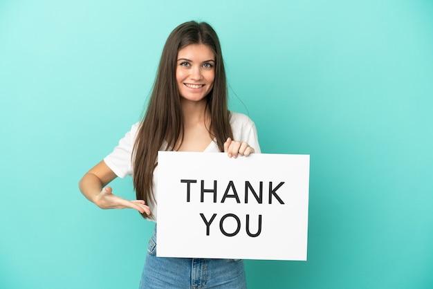 Junge kaukasische frau isoliert auf blauem hintergrund, die ein plakat mit dem text danke hält und darauf zeigt