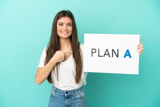 Junge kaukasische frau isoliert auf blauem hintergrund, die ein plakat mit der nachricht plan a hält und darauf zeigt