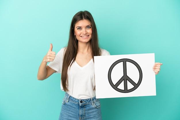 Junge kaukasische frau isoliert auf blauem hintergrund, die ein plakat mit friedenssymbol mit daumen nach oben hält
