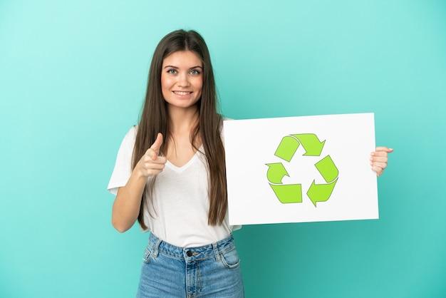 Junge kaukasische frau isoliert auf blauem hintergrund, die ein plakat mit recycling-symbol hält und nach vorne zeigt