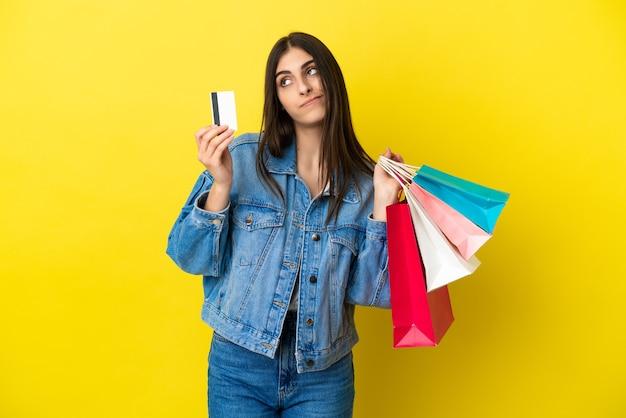 Junge kaukasische frau isoliert auf blauem hintergrund, die einkaufstüten und eine kreditkarte hält und denkt