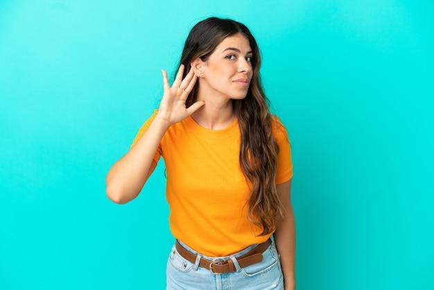Junge kaukasische frau isoliert auf blauem hintergrund, die etwas hört, indem sie die hand auf das ohr legt