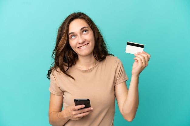 Junge kaukasische frau isoliert auf blauem hintergrund, die mit dem handy mit einer kreditkarte kauft, während sie nachdenkt