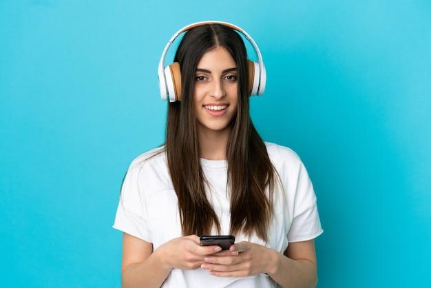 Junge kaukasische frau isoliert auf blauem hintergrund, die musik mit einem handy hört und nach vorne schaut