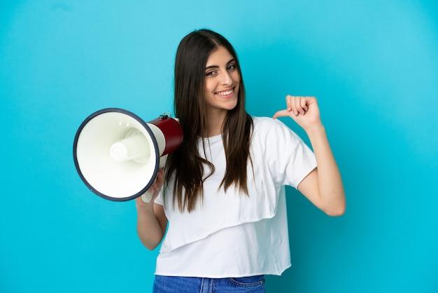 Junge kaukasische frau isoliert auf blauem hintergrund mit einem megaphon und stolz und selbstzufrieden