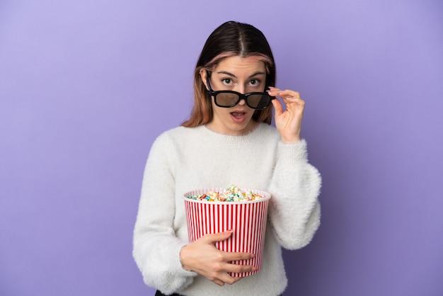 Junge kaukasische frau isoliert auf blauem hintergrund überrascht mit 3d-brille und hält einen großen eimer popcorncorn