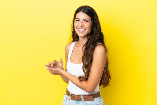 Junge kaukasische frau isoliert auf gelbem hintergrund applaudieren