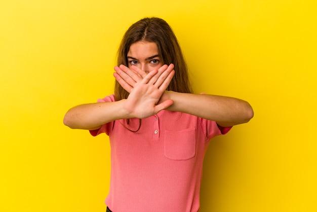 Junge kaukasische frau isoliert auf gelbem hintergrund, die eine verweigerungsgeste tut