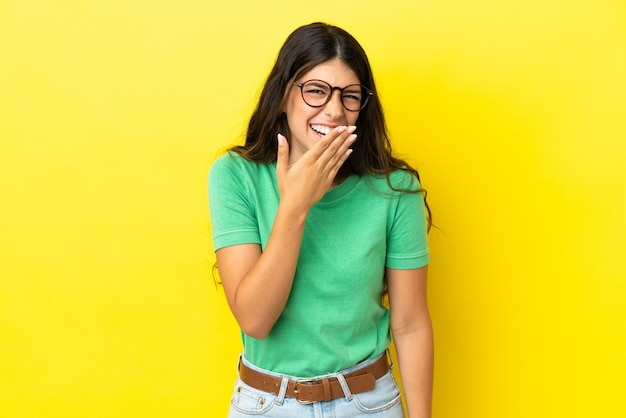 Junge kaukasische frau isoliert auf gelbem hintergrund glücklich und lächelnd, den mund mit der hand bedeckend