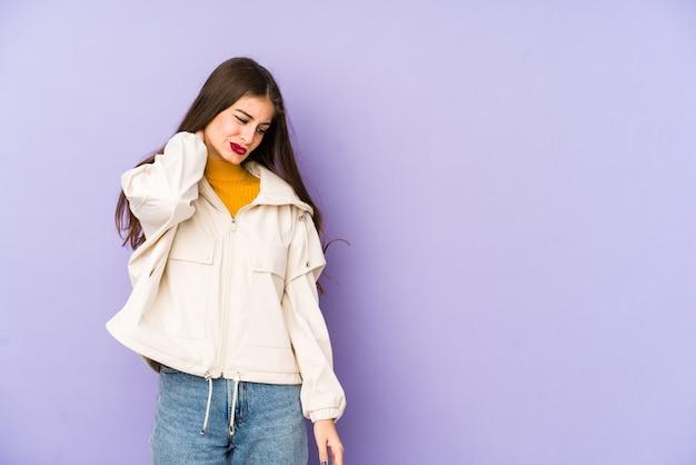 Junge kaukasische frau isoliert auf lila, die einen nackenschmerz aufgrund von stress, massage und berühren mit der hand hat.