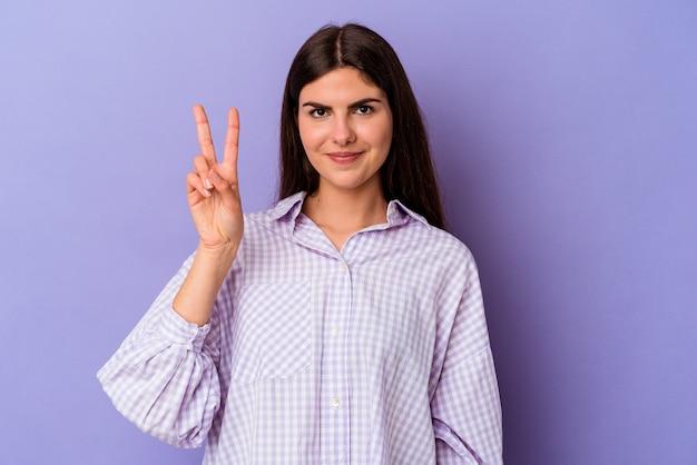 Junge kaukasische frau isoliert auf lila hintergrund fröhlich und sorglos, die ein friedenssymbol mit den fingern zeigt.