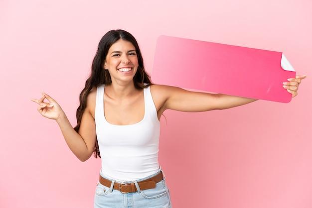 Junge kaukasische frau isoliert auf rosa hintergrund, die ein leeres plakat hält und auf die seite zeigt