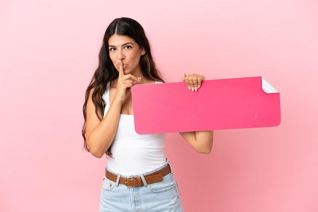 Junge kaukasische frau isoliert auf rosa hintergrund, die ein leeres plakat hält und stillegeste tut