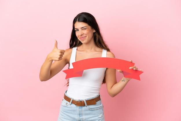 Junge kaukasische frau isoliert auf rosa hintergrund, die ein leeres plakat mit dem daumen nach oben hält