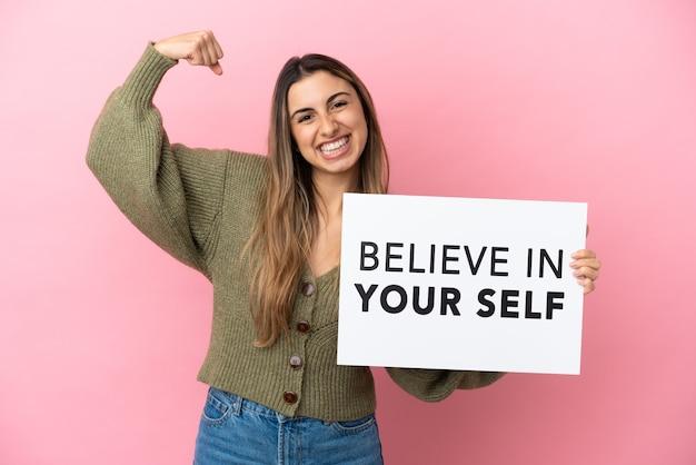 Junge kaukasische frau isoliert auf rosa hintergrund, die ein plakat mit dem text believe in your self hält und eine starke geste macht