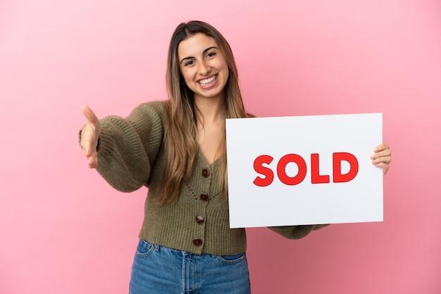 Junge kaukasische frau isoliert auf rosa hintergrund, die ein plakat mit dem text verkauft hält einen deal zu machen