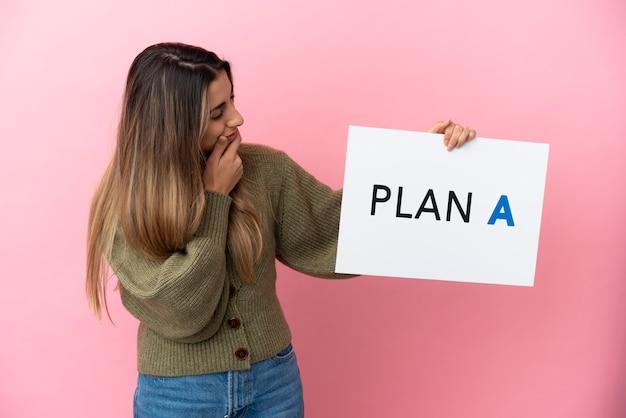 Junge kaukasische frau isoliert auf rosa hintergrund, die ein plakat mit der nachricht plan a hält und denkt