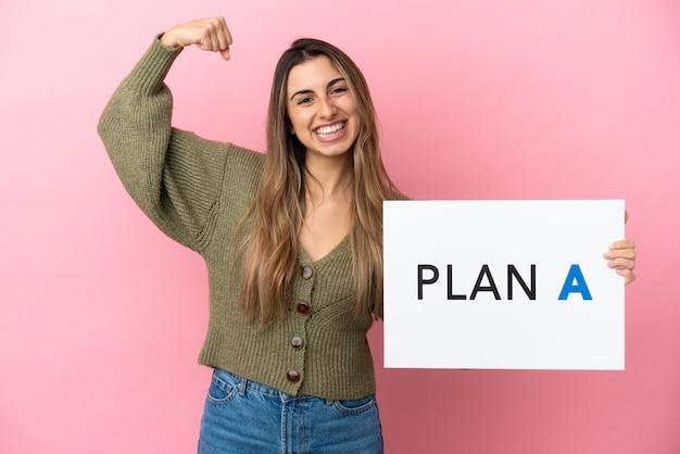 Junge kaukasische frau isoliert auf rosa hintergrund, die ein plakat mit der nachricht plan a mit starker geste hält
