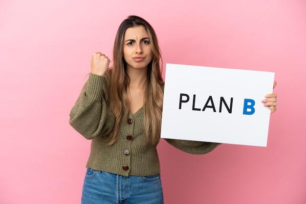 Junge kaukasische frau isoliert auf rosa hintergrund, die ein plakat mit der nachricht plan b hält und wütend