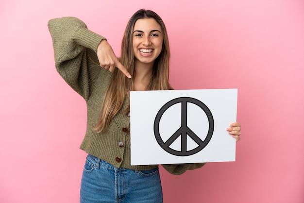Junge kaukasische frau isoliert auf rosa hintergrund, die ein plakat mit friedenssymbol hält und darauf zeigt