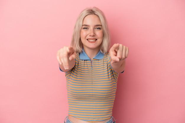 Junge kaukasische frau isoliert auf rosa hintergrund fröhliches lächeln, das nach vorne zeigt. Premium Fotos