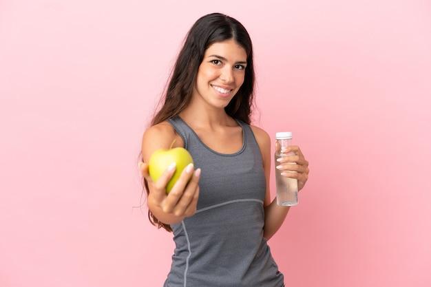 Junge kaukasische frau isoliert auf rosa hintergrund mit einem apfel und einer flasche wasser