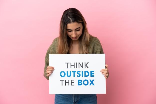 Junge kaukasische frau isoliert auf rosa hintergrund mit einem plakat mit text think outside the box