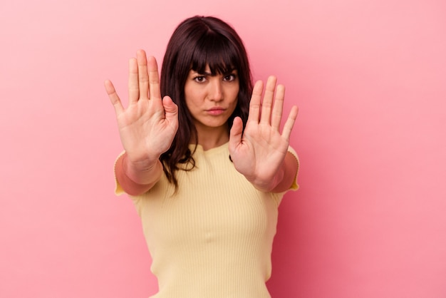 Junge kaukasische frau isoliert auf rosafarbenem hintergrund, die mit ausgestreckter hand steht und stoppschild zeigt und sie verhindert.
