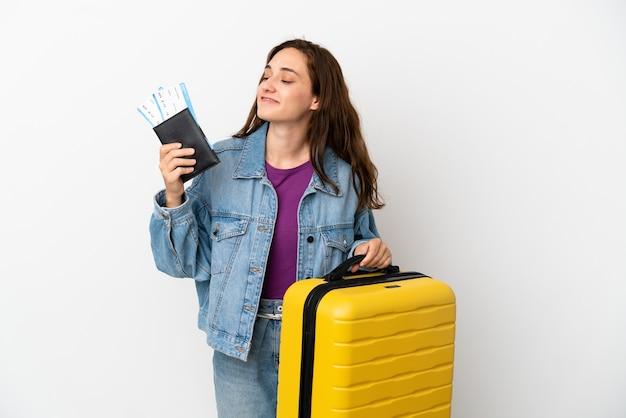 Junge kaukasische frau isoliert auf weißem hintergrund im urlaub mit koffer und reisepass