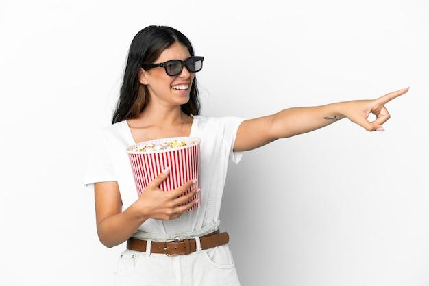 Junge kaukasische frau isoliert auf weißem hintergrund mit 3d-brille und hält einen großen eimer popcorn, während sie wegzeigt