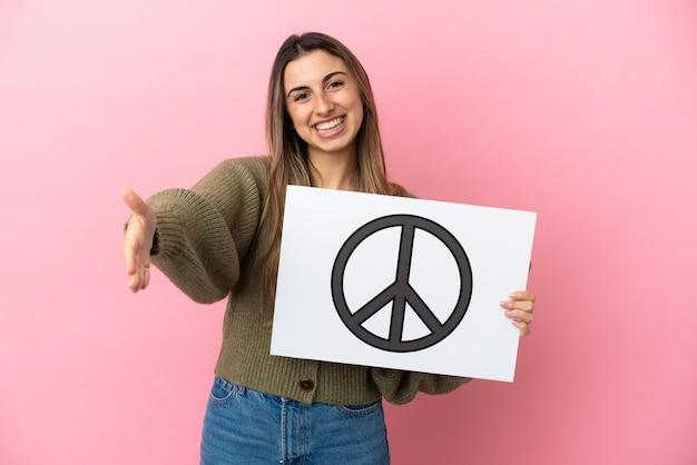 Junge kaukasische frau isoliert mit einem plakat mit friedenssymbol, das einen deal macht