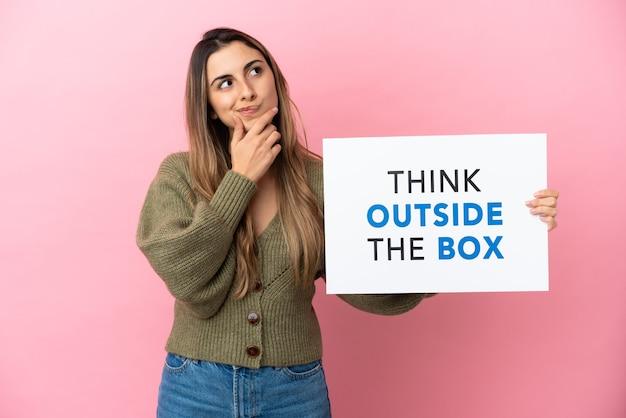 Junge kaukasische frau isoliert mit einem plakat mit text think outside the box und thinking