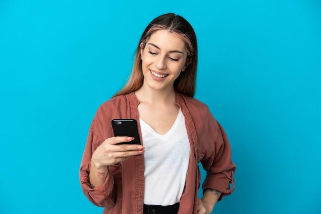 Junge kaukasische frau isoliert senden einer nachricht oder e-mail mit dem handy