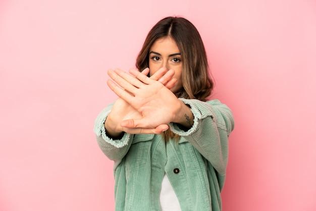 Junge kaukasische frau isoliert stehend mit ausgestreckter hand, die stoppschild zeigt