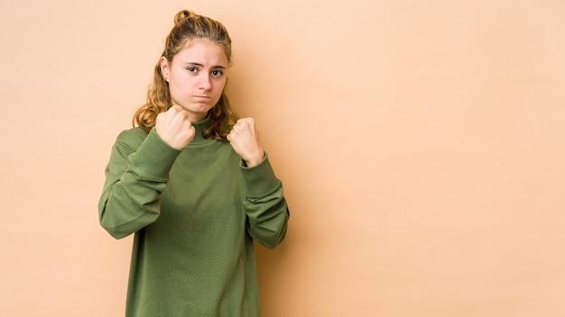 Junge kaukasische frau lokalisiert auf beige, die faust, aggressiven gesichtsausdruck zeigt.