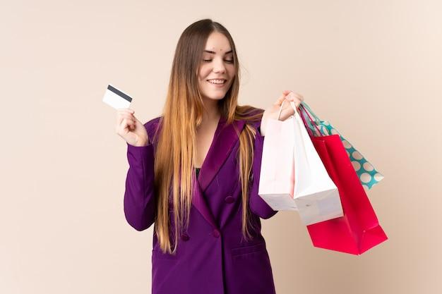 Junge kaukasische frau lokalisiert auf beige wand, die einkaufstaschen und eine kreditkarte hält