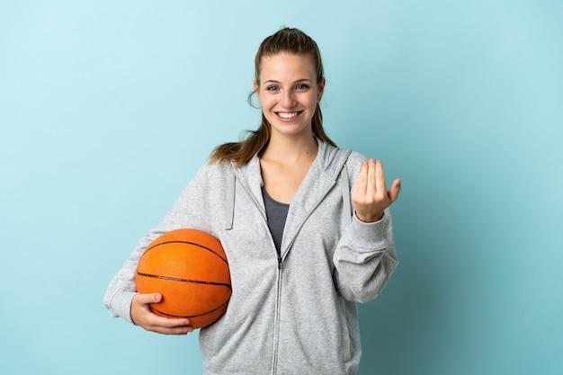 Junge kaukasische frau lokalisiert auf blau, das basketball spielt und kommende geste tut