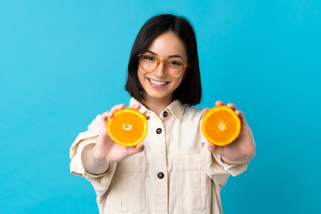 Junge kaukasische frau lokalisiert auf blau, das eine orange hält