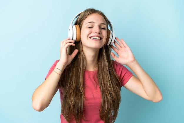 Junge kaukasische frau lokalisiert auf blau hörende musik und gesang