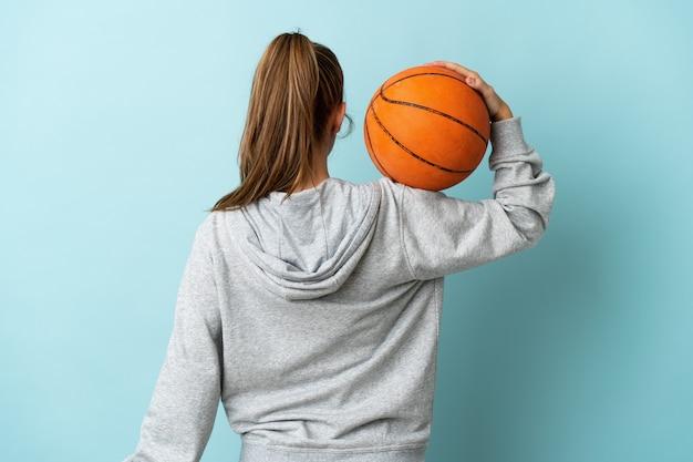 Junge kaukasische frau lokalisiert auf blau spielendem basketball in der hinteren position