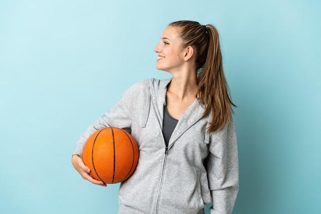 Junge kaukasische frau lokalisiert auf blau spielendem basketball