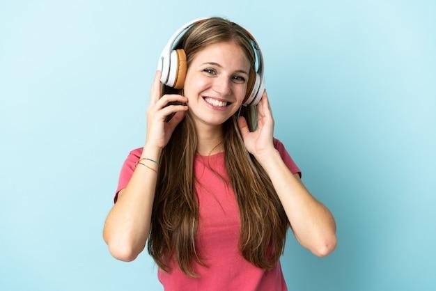 Junge kaukasische frau lokalisiert auf blaue hörende musik